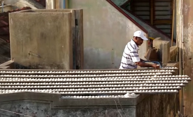 He aligns piles of rice on his roof – you won't believe why