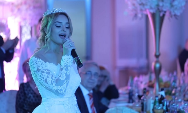 The bride and groom sing a love song in a beautiful duet